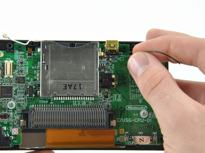 Position the antenna cable with its connector facing up and away from the motherboard using a spudger to hold it down lightly in the gap between chips on the motherboard.