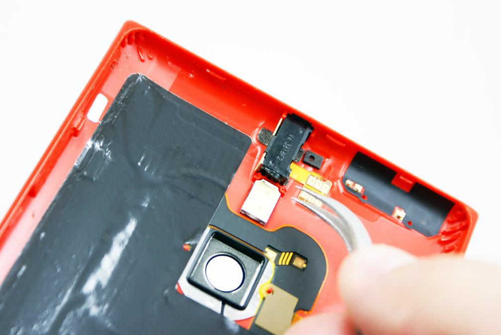 4. Now, use a heat gun or blow dryer to soften the adhesive securing the headphone jack to the rear cover.