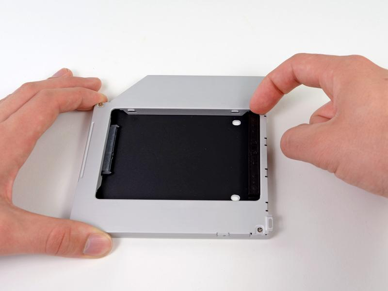 Paso 18 Dual Hard Drive Remove the plastic spacer from the optical bay hard drive enclosure by