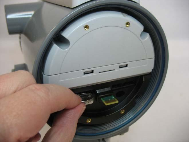 Figure 5-6: Removing/Replacing the Coin Cell Battery 5. Insert the new coin cell battery in the slot. The positive side (+) must be on top. 6. Replace the HMI module. 7. Replace the front end cap.