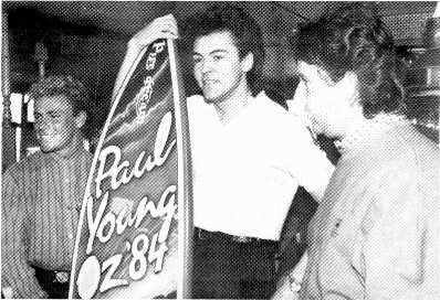 Down Under. Paul Young, center, receives a surfboard from Dennis Handlin, CBS Records' managing director, during his recent Australian concert tour.