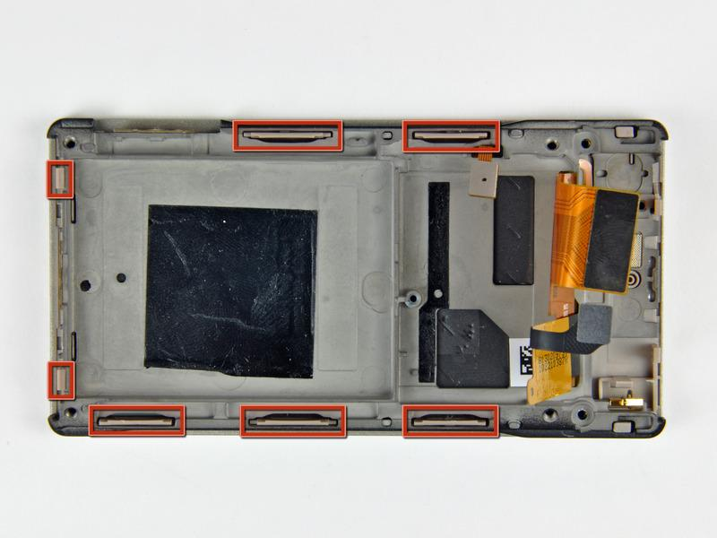 Step 17 The inner chassis attaches to the front case by several clips around its perimeter (shown in red).